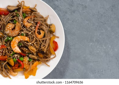 spicy buckwheat noodles with seafood and vegetables on a gray background, top view, horizontal