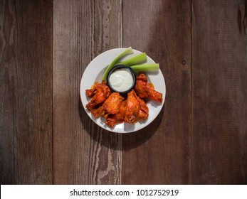 Spicy Buffalo Wings on plate with Blue cheese and celery sticks.