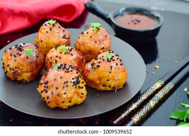Spicy chicken balls in sweet chilli glaze on a metal tray