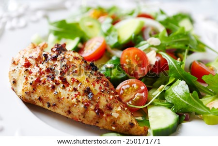 Spicy chicken breast with cherry tomatoes, cucumber, white onion, leek and fresh rocket. Home made tasty food. Concept for a healthy and hearty meal. Close up. Paleo diet recipe