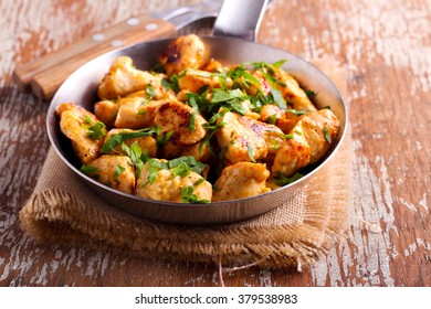 Spicy chicken breast pieces in a pan