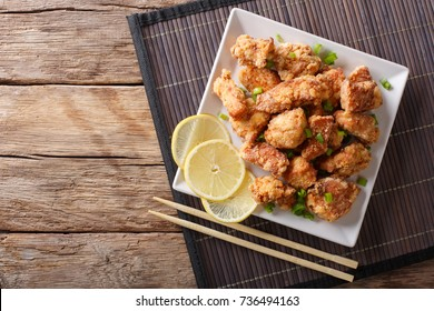 Spicy chicken karaage with lemon and green onion close-up on the table. horizontal top view from above