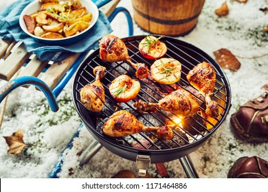 Spicy chicken legs grilling on a seasonal winter BBQ outdoors on a cold day in the snow with potato wedges and halved nectarines or apricots in a close up high angle view