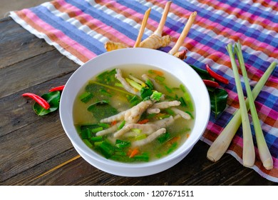 Spicy chicken legs Soup in white cup on wooden table