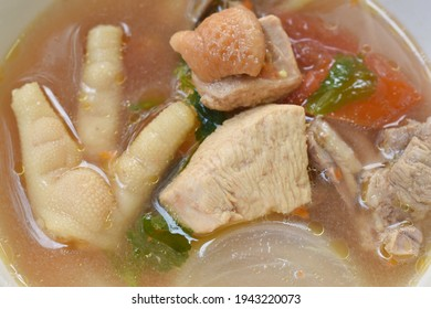 spicy chicken meat and foot in tom yum soup on bowl