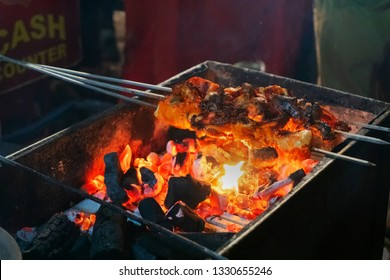 Spicy chicken seekh kababs are being grilled with charcoal in barbeque with metal skewers,at evening for sale as street food in Old Delhi market. It is famous for spicy non vegetarian street foods.
