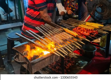Spicy chicken seekh kababs are being grilled with heat in barbeque with metal skewers,at evening for sale as street food in Old Delhi market. It is famous for spicy Indian non vegetarian street foods.
