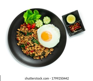 Spicy Chicken  Stir Fried with Basil,chili and Rice ontop Fried Egg decorate Carved chili and vegetable served Chili fish Sauce Thai Food style topview