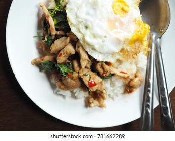 "Spicy chicken Thai basil stir-fry and fried egg. Popular Thai food ""Pad Krapow Gai Kai Dao"" to eat with rice. (top view, close up, selective focus)"