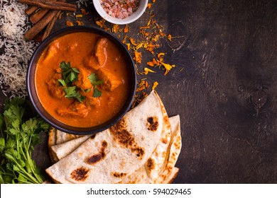 Spicy chicken tikka masala in bowl on rustic wooden background. With rice, indian naan butter bread, spices, herbs. Space for text. Traditional Indian/British dish. Top view. Indian food. Copy space
