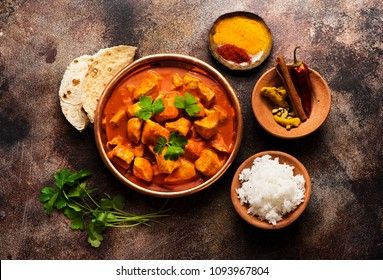 Spicy chicken tikka masala with rice, indian naan bread, spices, herbs. Traditional Indian dish.