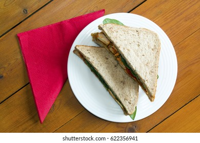 Spicy chicken tikka sandwich on a table with a napkin from an overhead perspective