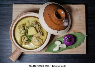 """Spicy chicken with tumeric and coconut milk in a clay pot. Also known as """"AYAM MASAK LEMAK CILI API"""" in Malaysia. Common Minang food in Negeri Sembilan, Malaysia."""