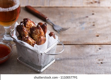 Spicy chicken wings prepared on barbecue on the wooden table with glass of beer