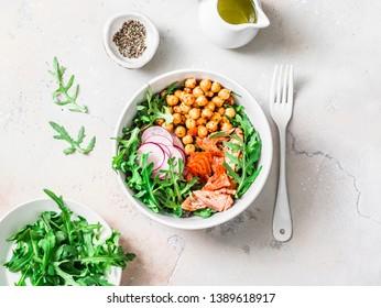 Spicy chickpeas, baked salmon, crispy radish, arugula salad on a light background, top view