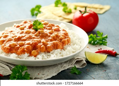 Spicy chickpeas curry with rice, tomato and Poppadoms in white plate. Healthy tasty vegetarian food