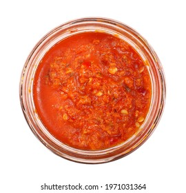 Spicy chili pepper sauce in galss jar, dip made from milled paprika with extra virgin olive oil, isolated on white background, top view