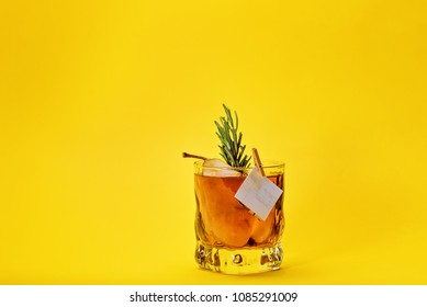 spicy cocktail with rum, pear and apple juice, yellow background