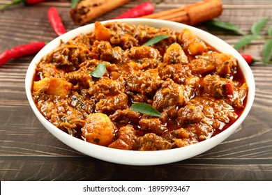 Spicy cooked meat curry roast  served in ceramic bowl over a rustic wooden kitchen table.