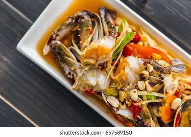 Spicy crab papaya salad, Sea Crab Somtum Salad, Thai food on black wood