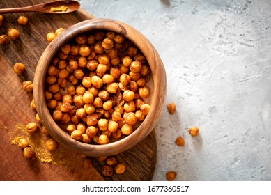 Spicy crispy roasted chickpeas with paprika, curry and hot chili pepper in a bowl, selective focus, top view, copy space. Tasty vegetarian and vegan chickpea snack, free space for text.