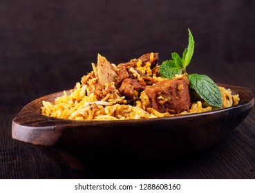Spicy and delicious mutton biryani on wooden background