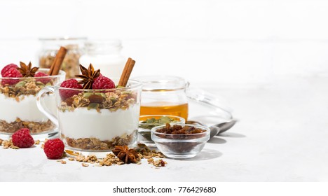 spicy dessert with sweet granola, raspberries and yogurt in the glass on white background, closeup