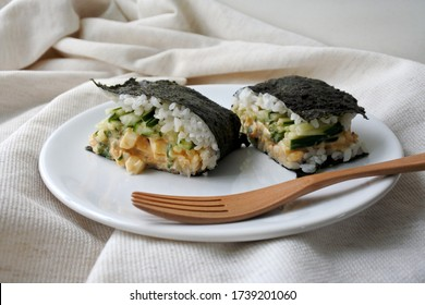 Spicy egg salad and cucumber Onigiri sandwiches (Japanese sushi rice balls) on a white plate with a wooden fork. Light background. Close-up. Free space to place text.