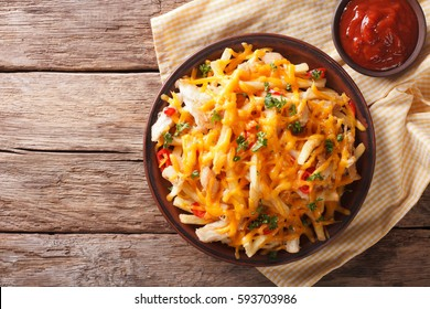 Spicy fast food: French fries with cheddar cheese, chili and chicken fillet close-up on a plate. horizontal view from above