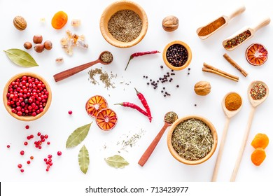 Spicy food cooking with spices and dry herbs white kitchen desk background top view pattern