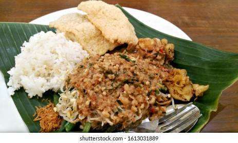Spicy gado gado or pecel in Solo, Java, Indonesia, with peanut sauce, vegetables and rice on a banana leaf
