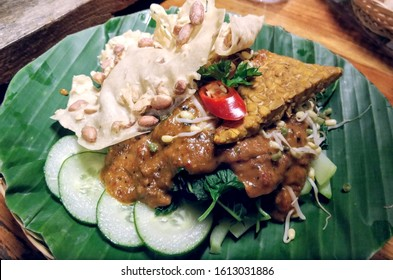 Spicy gado gado salad with peanut sauce, cucumber, sprouts and rempeyek on a banana leaf