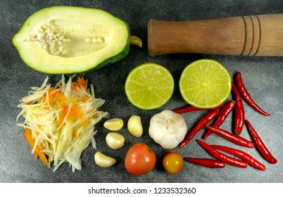 Spicy Green Papaya Salad, Thai style spicy food, Som Tum food concept, props decoration Garlic, red pepper, lemon, tomatoes, on stone background.Top view Copy Space.