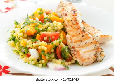 Spicy grilled chicken with fresh vegetables and couscous