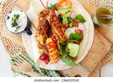 Spicy grilled chicken skewers with fresh salad on tortillas