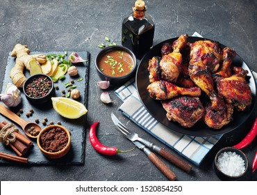 Spicy Grilled Jamaican Jerk Chicken drumsticks and thighs on a black platter on a concrete table with ingredients, horizontal view from above