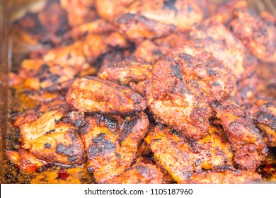 Spicy Grilled Jerk Chicken on the barbecue - style of cooking native to Jamaica - Food Street Market