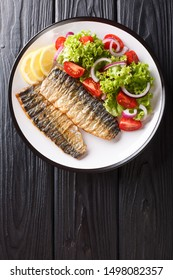 Spicy grilled mackerel fillet with lemon and fresh vegetable salad close-up on a plate on the table. Vertical top view from above