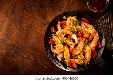 Spicy grilled prawns with garlic, fresh herbs and red bell peppers served as an appetizer in an old frying pan with a side dish of chili tomato sauce, overhead on wood with copy space