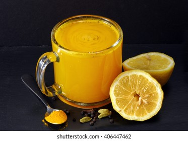 Spicy healthy Haldi or Turmeric and pepper antioxidant drink with lemon on a moody background.