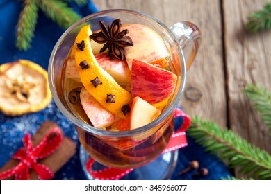 Spicy hot drink (cider, punch, tea) with apple, orange, cinnamon, star anise for Christmas and winter holidays