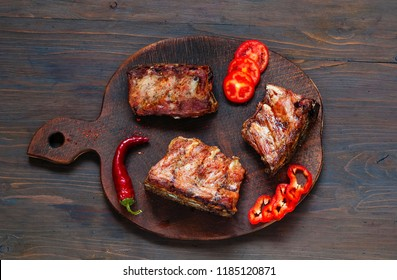 Spicy hot grilled spare ribs from BBQ served with  hot chili pepper and lime on dark wooden background.  Banner.  Top view,  copy space, flat lay.