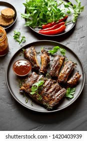 Spicy hot grilled spare ribs on plate over black stone table. Tasty grilled meat.