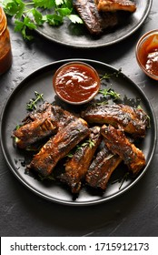 Spicy hot grilled spare ribs on plate over black stone background. Tasty bbq meat.