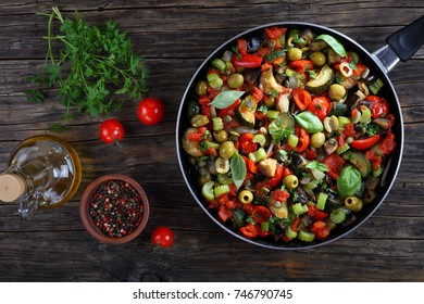 spicy Italian Caponata with vegetables, green olives, capers, celery and herbs on skillet on dark wooden table with ingredients on background, view from above,