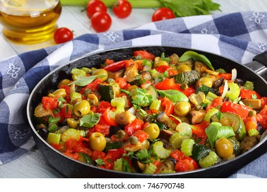 spicy Italian Caponata with vegetables, green olives, capers, celery and herbs on skillet on wooden table with kitchen towel and ingredients on background, horizontal view from above, close-up