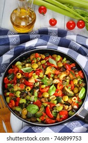 spicy Italian Caponata with vegetables, green olives, capers, celery and herbs on skillet on wooden table with kitchen towel and ingredients on background, vertical view from above, close-up