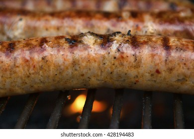 Spicy Italian pork sausages cooking on a backyard grill. Images shows the grill, flame and bubbling, delicious and nearly ready to eat meat.