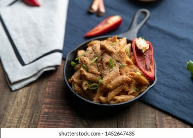 Spicy Mac and Cheese in Personal Cast Iron Pan on Dark Wooden Surface Board with Off-White and Dark-Blue Napkins, Garnished with Spicy Red Peppers, Scallions, and Bread Crumbs. Studio Light.