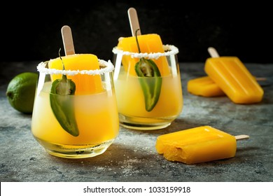 Spicy mango popsicle margarita cocktail with jalapeno and lime. Mexican alcoholic drink for Cinco de mayo party